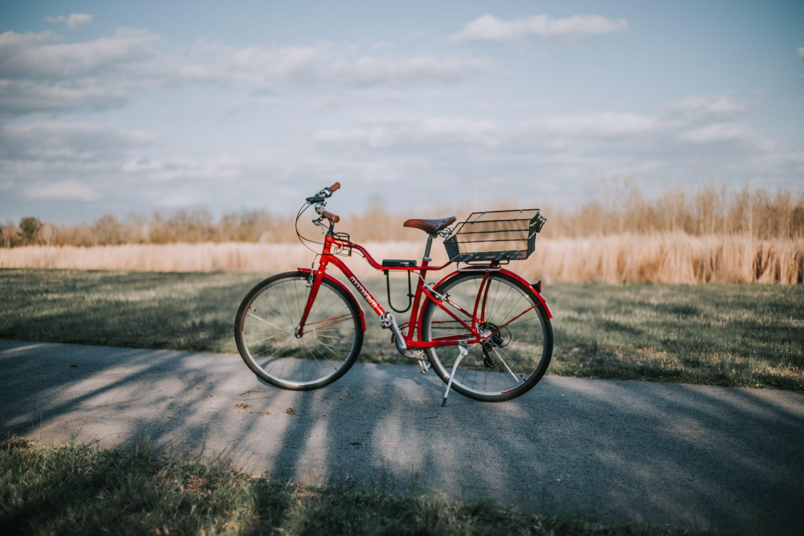 vélo rouge avec panier devant champs